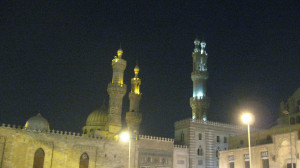 Sitting at our café, we watch the lighted towers of El Azhar Mosque as darkness falls