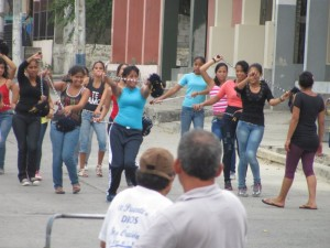 In Bahia, high school girls practice a baton routine as the boys drum-line rehearses